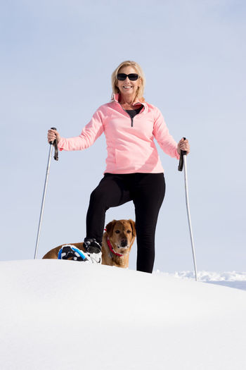 Deby & Molly Blond Hair Clear Sky Dog Exercising Full Length Fun Happiness Labrador Retriever Leisure Activity Lifestyles Low Angle View Mature Adult One Person Only Women People Pink Color Smiling Snow Snowshoeing Sunglasses Winter