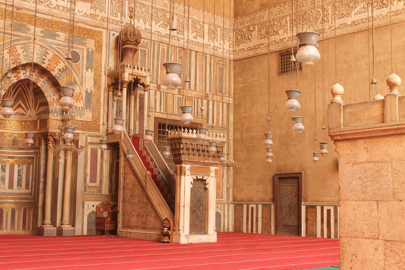 Inside the sanctuary of the Sultan Hasan mosque in Cairo, showing the minbar, mihrab, and hanging mosque lamps, with calligraphic inscription frieze Cairo Islam# Architecture Built Structure Mihrab# Minbar# Mosque# No People
