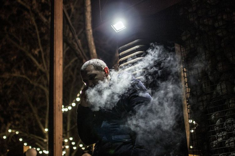 Man smoking by illuminated lights at night