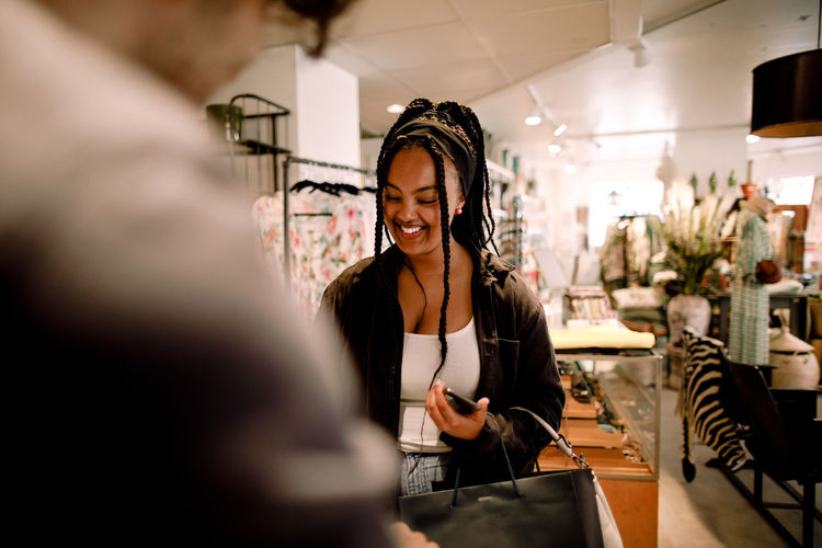 Portrait of smiling young woman using smart phone at store