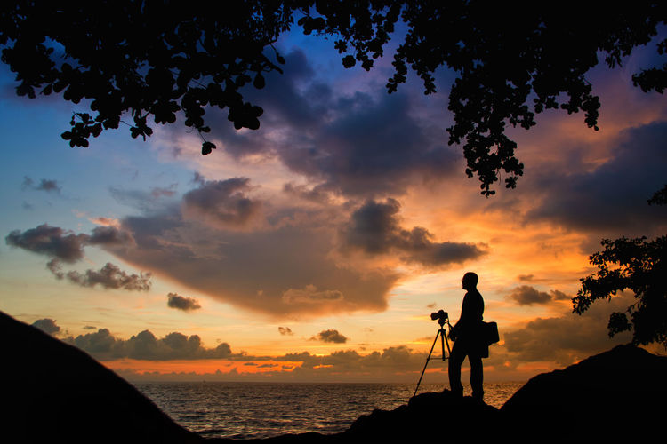 Silhouette man with camera on rock by sea against sky during sunset
