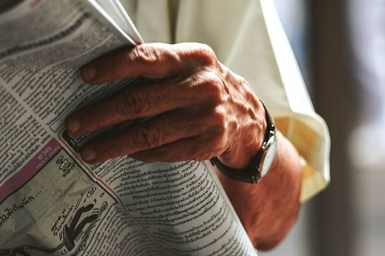 Midsection of man reading newspaper