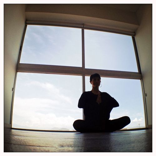 A woman doing Yoga exercises in her modern living room. Woman Exercise Pilates Yoga Meditation Window