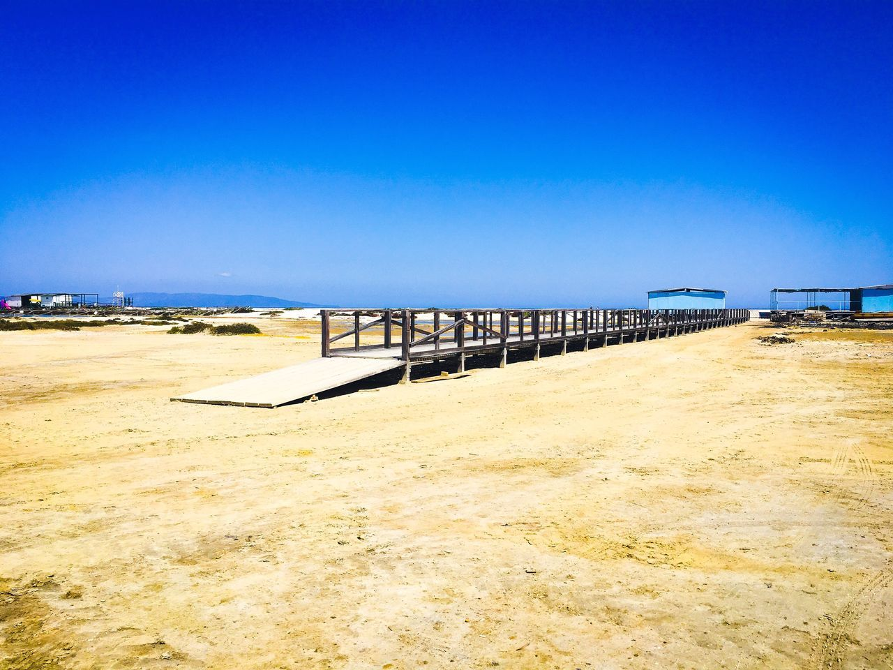 beach, sand, day, clear sky, nature, copy space, tranquility, tranquil scene, sea, scenics, outdoors, blue, sunlight, no people, water, beauty in nature, horizon over water, built structure, landscape, architecture, sky