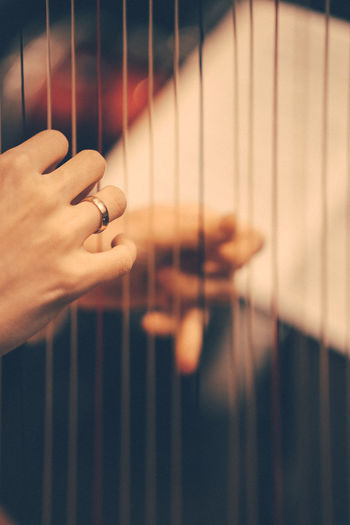 Cropped hands playing string instrument