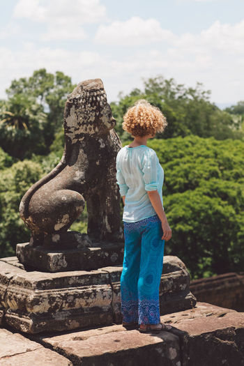Woman Standing By Old Ruin Statue