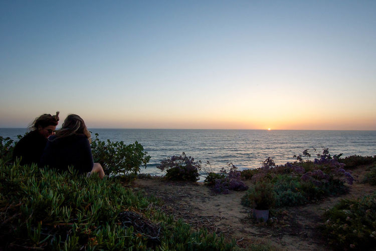 Two girls watching the sunset in Encinitas, ca. Sea Horizon Over Water Nature Outdoors Scenics Tranquility Travel Destinations Clear Sky People Women Around The World Green Color Grassy Sunset Beauty In Nature Ocean Waves Oceanphotography Ocean View San Diego Enchanted  Encinitas California Beach Sunsetporn Sea And Sky Looking Into The Future