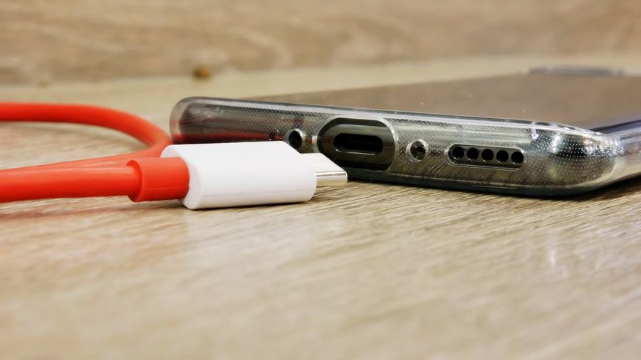 Close-up of mobile phone and charger on table