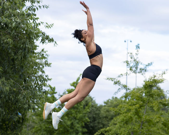Full length of young woman in mid-air against trees