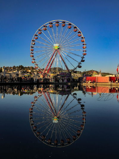 Amusement Park Amusement Park Ride Architecture Blue Building Exterior Built Structure City Clear Sky Day Ferris Wheel No People Outdoors Reflection Sky Water Waterfront