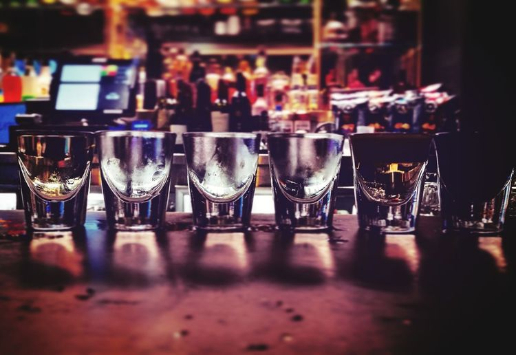 Close-up of empty shot glasses on bar counter