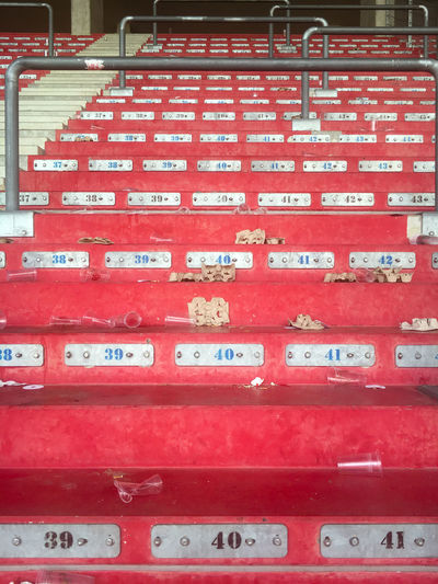 Empty red painted stand in a sports stadium with some rubbish after a match Red Communication Text No People Western Script Close-up Day Stack Full Frame In A Row Backgrounds Outdoors Arrangement Pattern Stadium Stadium Stands Standing Sports Sport Venue Arena Rubbish Waste