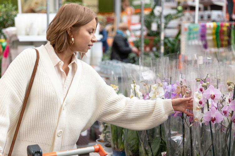 Woman touching flowering plants at florist shop