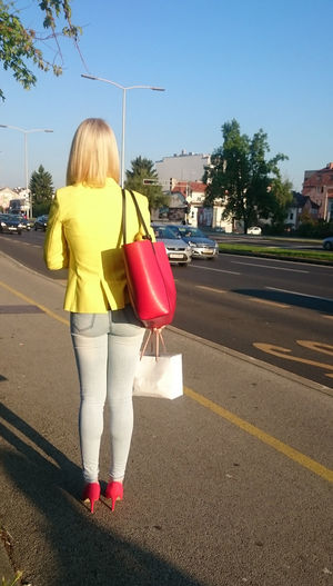 Rear view of young woman standing on road