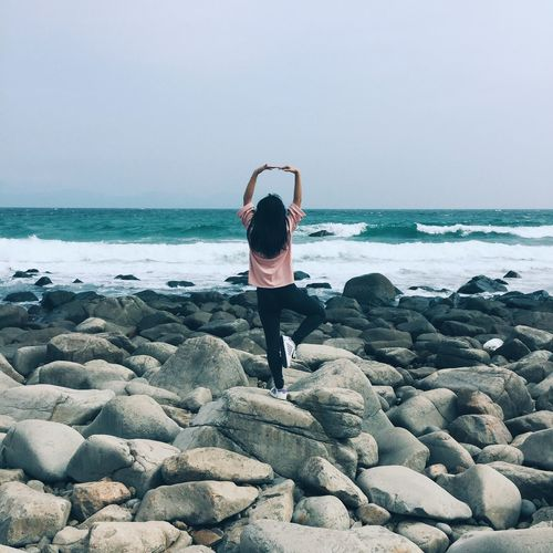 WOMAN STANDING IN TREE POSE ON ROCKY SHORE