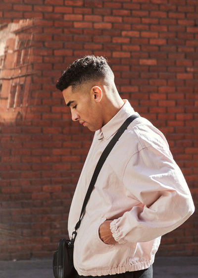 Side view of young man standing against brick wall