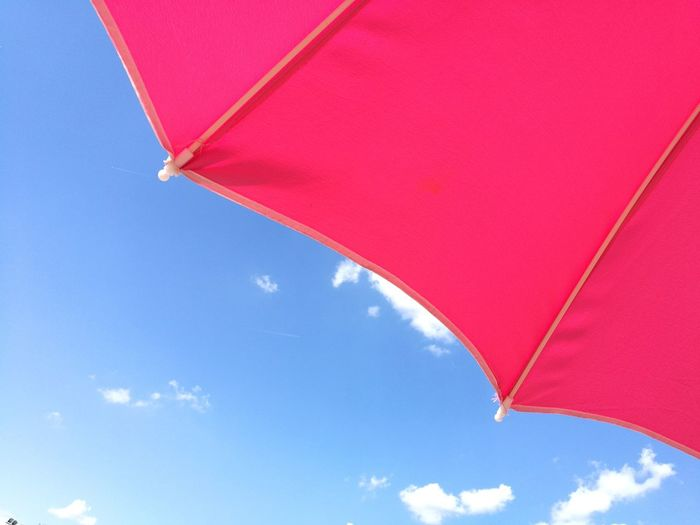 Low angle view of red umbrella against blue sky