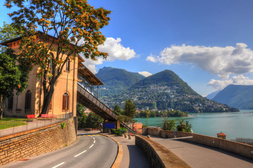 Street and cable railway with mountain and alpine lake Lugano in Ticino, Switzerland. Alpine Lake Architecture Beauty In Nature Blue Sky Bridge - Man Made Structure Building Exterior Cable Railway City Cloud - Sky Day Famous Place Lake Lake Lugano Landscape Mountain Mountain Range No People Outdoors Station Train Street Sunny Swiss Alps Transportation Travel Destinations Tree