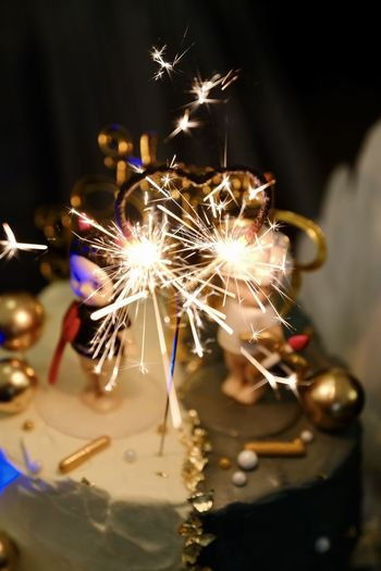 Close-up of sparklers on cake