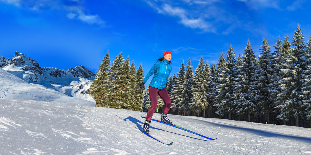 Woman skiing on ice at mountain slope against sky