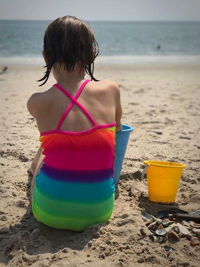 Rear view of girl playing on sand at beach during summer