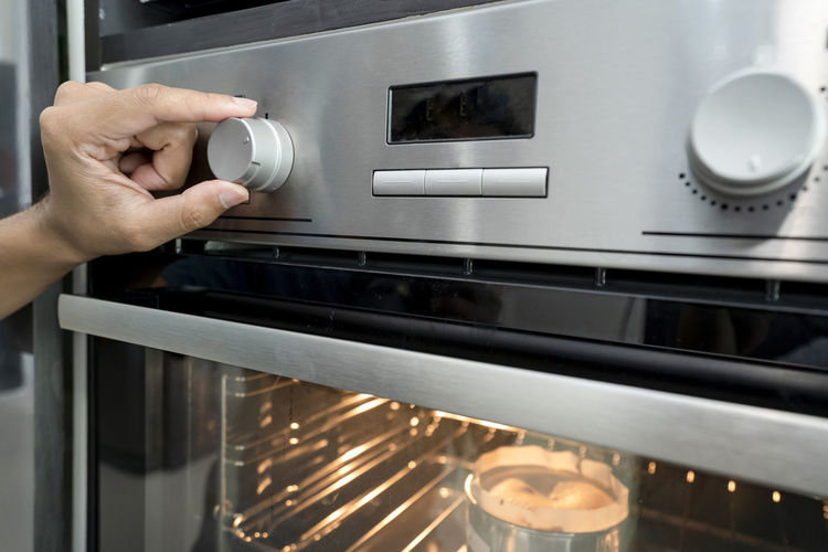 Hand of using microwave oven control heating and timer in kitchen room home modern Human Hand Hand Human Body Part Appliance Oven Kitchen One Person Domestic Room Indoors  Domestic Kitchen Home Stove Technology Lifestyles Food And Drink Holding Focus On Foreground Unrecognizable Person Food Finger Inserting Push Button Human Limb