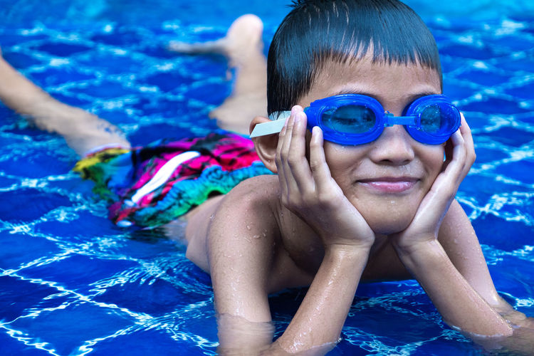 Portrait of asian boy ware a blue glasses, smilling and put chin on hands. Lay in swimming pool and blue refreshing water Boy Face Smile Smiling Asian  Happy Happiness Hand Goggles Blue Swim Swimming Pool Kid Young Arm Play Childhood Glasses Child Healthy Fun Water Cool Still Cute Summer Splash Arms Sport Victory Gesture person Outdoor Active Holiday Vacation Excited Fit Playing Activities Lay Enjoy Lifestyle Relax Emotion Showing Swimmer Portrait Wet