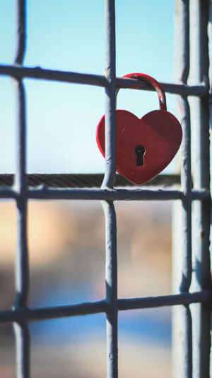 Close-up of padlocks on fence against sky