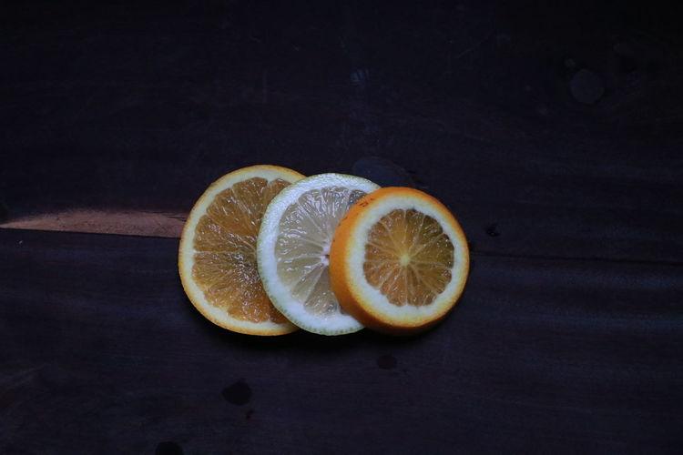 Close-up of orange on table against black background