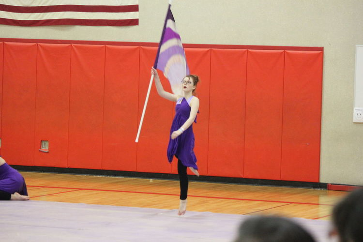 Ballet dancer holding flag while performing winter guard in gymnasium