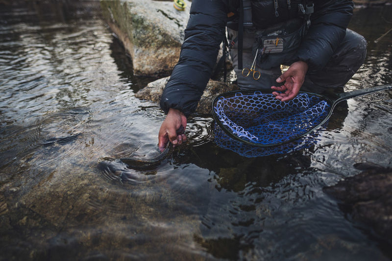 Man holding rock in river