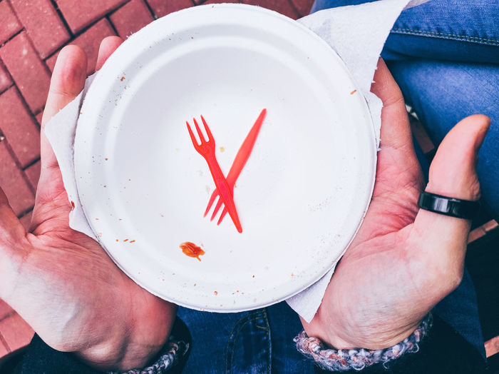Directly above view of man holding empty disposable plate in hand