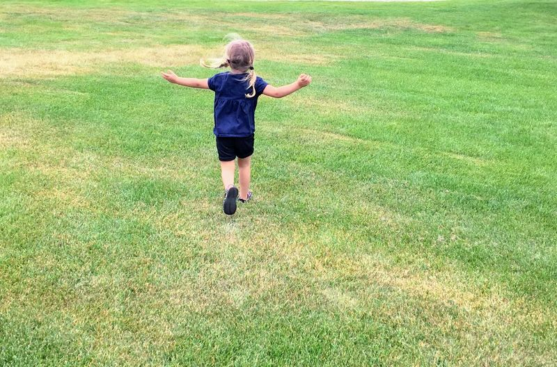 Rear view of girl running on field