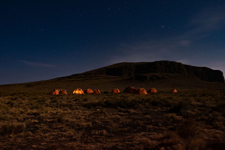 Camping on top of mountain on a starry night  with glowing tent