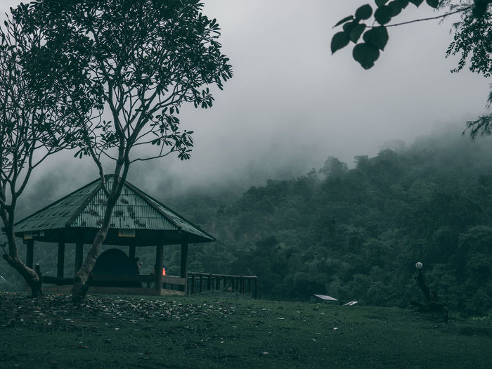 Built structure by trees against sky during rainy season