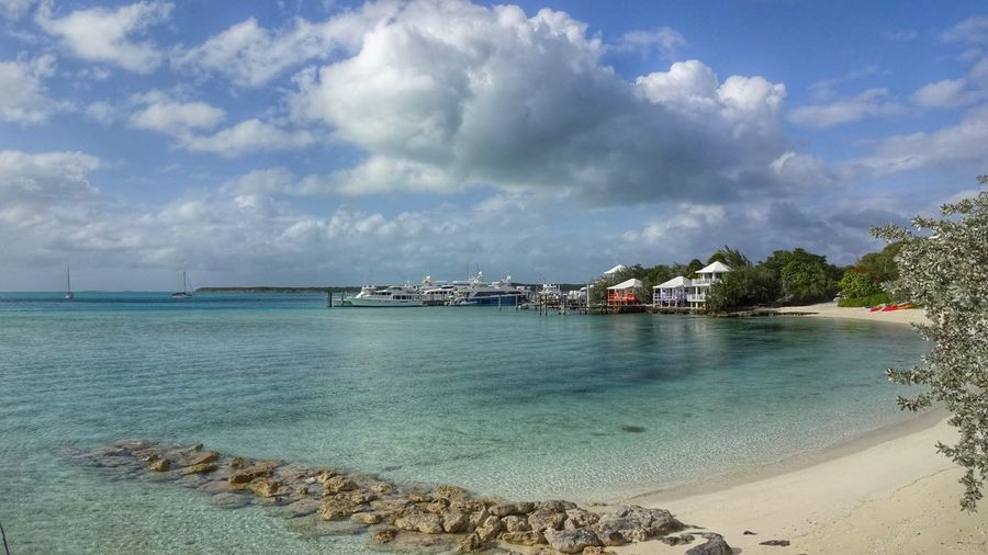 Boats moored by houses at staniel cay against sky