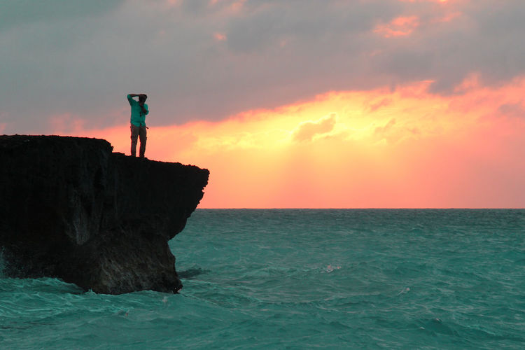 Rear view of silhouette man standing on rock by sea against sky