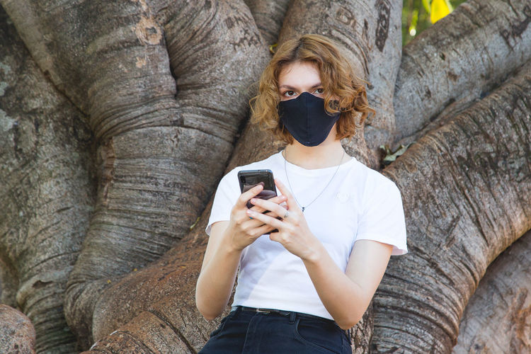Portrait of young woman using mobile phone while standing against tree