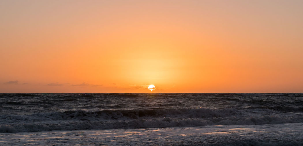 Photo of centered position sunrise at a beach with an orange and pink sky. Beach Beauty In Nature Horizon Horizon Over Water Idyllic Land Motion Nature No People Orange Color Outdoors Scenics - Nature Sea Sky Sun Sunset Tranquil Scene Tranquility Water Wave