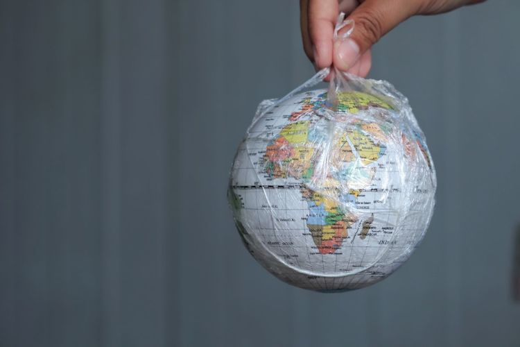 Cropped hand holding globe in plastic bag