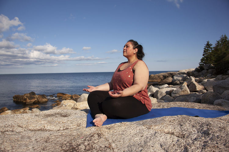 Young woman sitting on rock at beach against sky