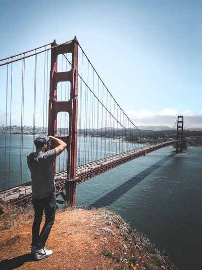 Rear view of man standing by bridge against sky