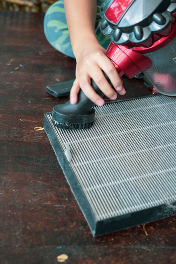 A young boy is cleaning the air filter sheet with the vacuum.
