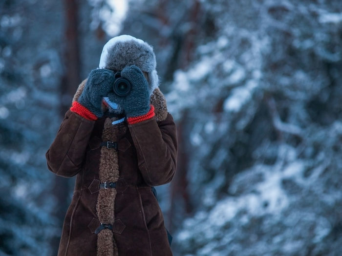 Woman photographing through camera while wearing warm clothing during winter