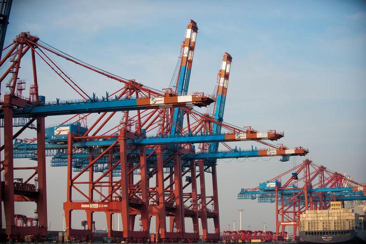Cranes At Dock Yard Against Sky