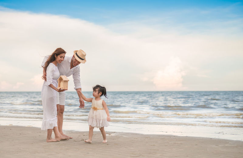 Full Length Of Couple With Daughter At Beach Against Sky