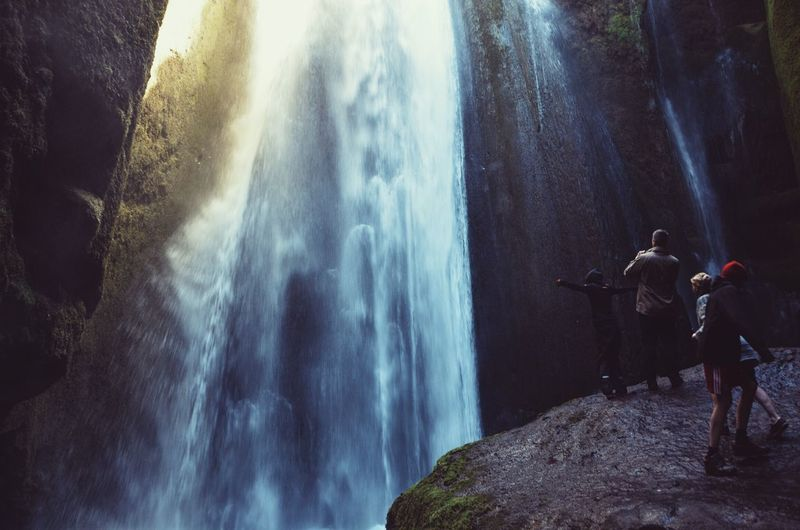 Man with children standing by waterfall
