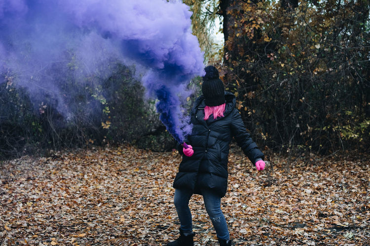 Woman wearing mask while holding distress flare in forest