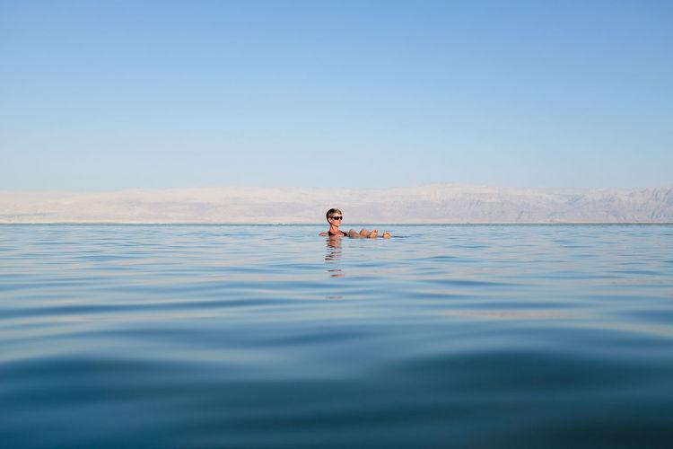 Woman relaxing in sea against sky