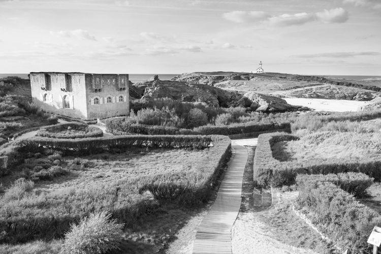Footpath leading towards castle against sky